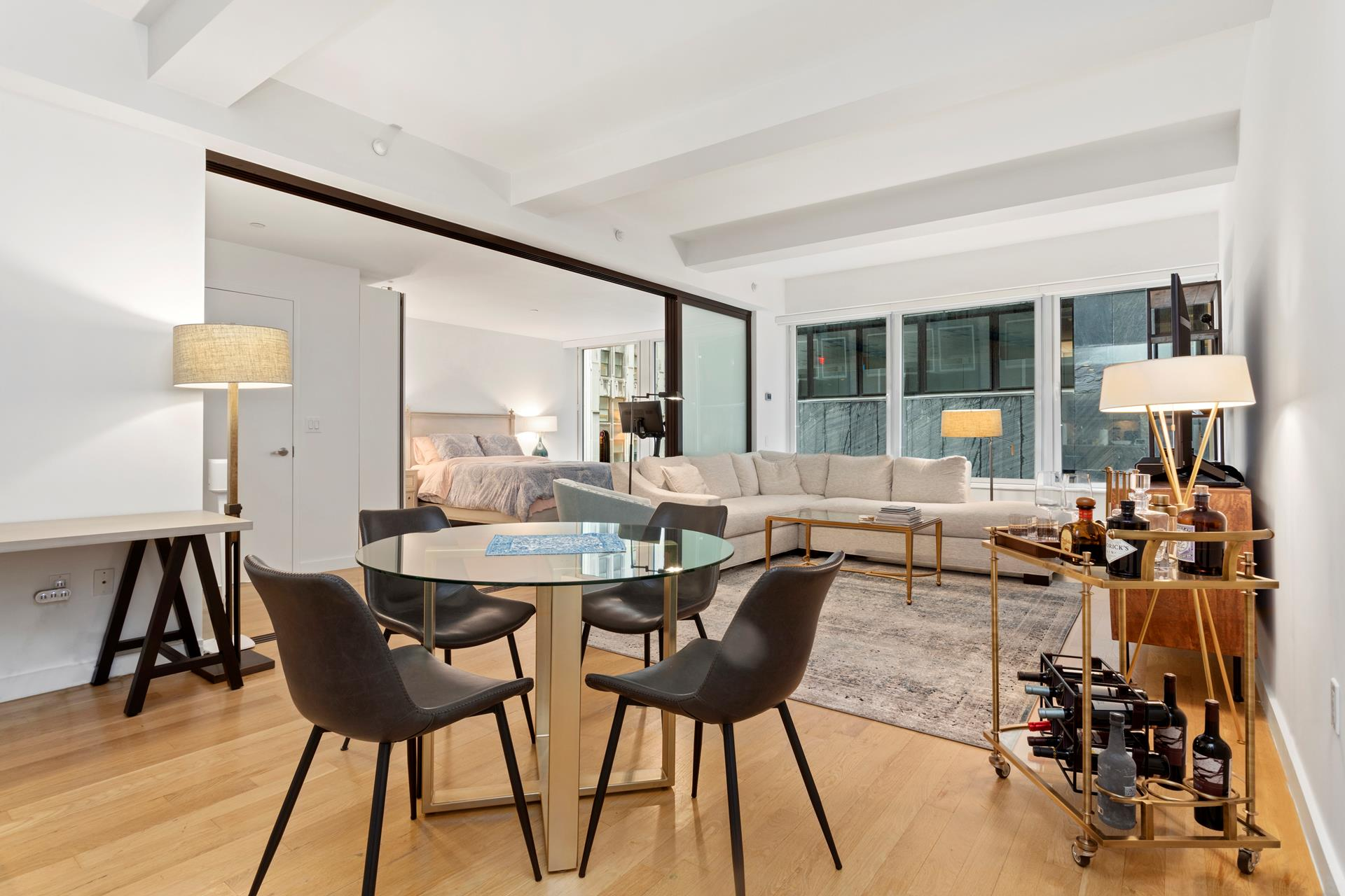 A stunning and functional condo with immaculate finishes and an abundance of natural light, this convertible 2-bedroom, 2-bathroom home sits in the heart of the Financial District. Features of this 1,072 sq. ft. apartment include white oak hardwood floors, ceilings over 9-ft, extra-large double-paned windows, and a large home office, custom black out shades in the master, motorized shades in the living room and a modern open plan layout. This home is incredible for those seeking a large loft space with bedrooms! The gourmet open kitchen is a masterpiece and is outfitted with stainless steel top of the line appliances, Liebherr refrigerator, sleek white lacquer kitchen cabinets and quartz countertops, plus a large island including dishwasher and double-depth sink. It opens to a great room with space to entertain and relax. Both the master bedroom and second bedroom offer generous amounts of space that have been fitted high quality sliding doors in dark stained wood and translucent fiberglass. The master bedroom suite was reconfigured to open directly into the living room, maximizing the width of the entire apartment and expansive set of windows. It has upgraded finishes, which include a custom built-in storage and a walk-in closet. The master ensuite bath features a dual vanity, as well as Kohler and Watermark fixtures, Toto toilets, and classic subway tiling. The oversized bonus room is perfect for a second bedroom, home office, or even a nursery. For convenience and efficiency, the entire home is equipped with a Smart Thermostat system allowing you to control the climate all through a smartphone or tablet at any time. Individual unit washer/dryers are permitted! Amenities are located on the Penthouse-level and include a double-height lounge overlooking a landscaped terrace with an outdoor fireplace and wet bar including a barbeque grill available all year round, a light-filled fitness center, billiards table, and common laundry. The building is excellently maintain