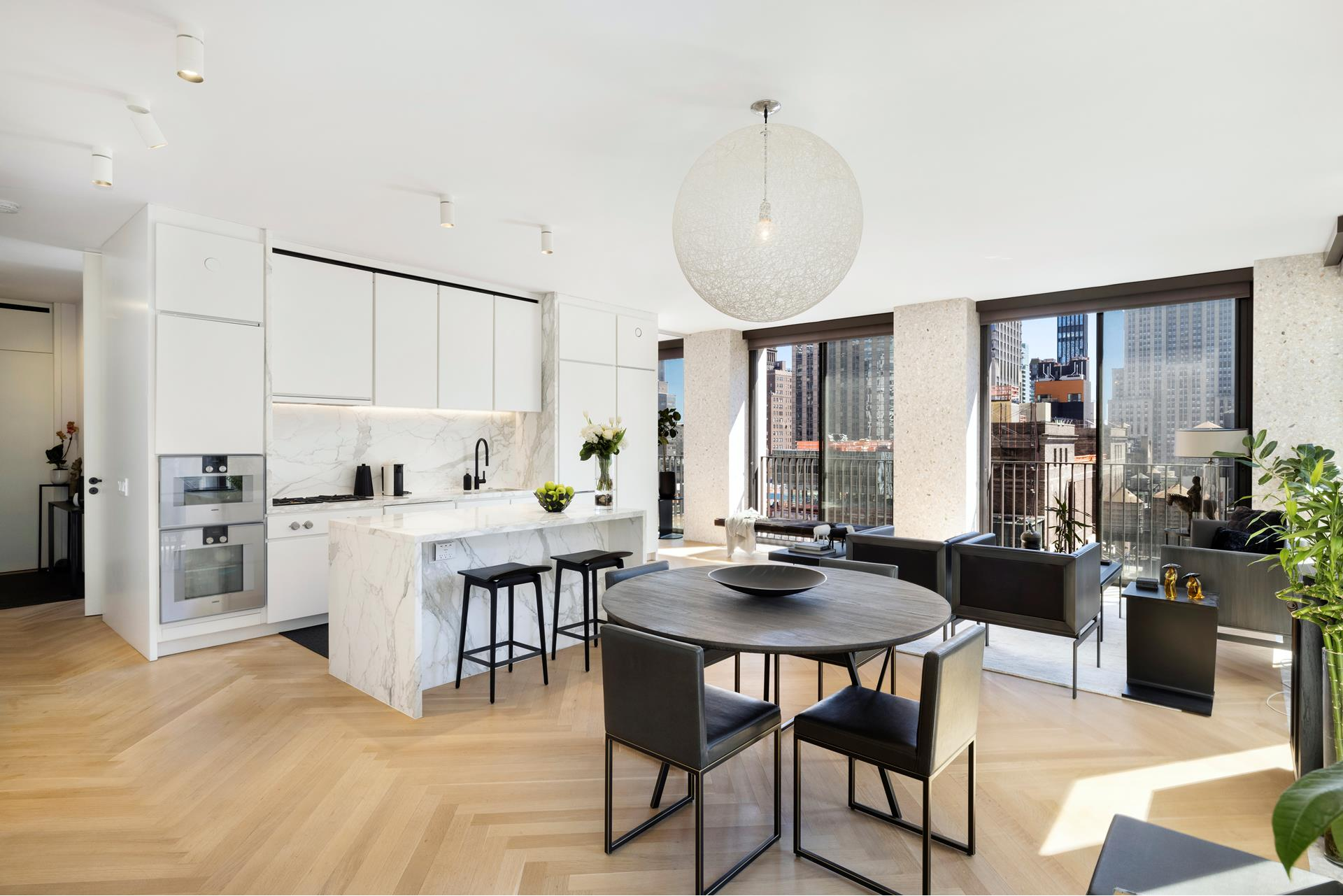 Welcome home to The Bryant! This 1,329 sq ft corner 2 bed 2.5 bath offers an abundance of natural light through 14 floor-to-ceiling windows that open completely on the south side to Juliet balconies - overlooking an amazing view of the Empire State Building.    The custom terrazzo facade transitions seamlessly into the interiors, creating crisp architectural frames to the windows and a border for the heated oak herringbone floors. The residence's bespoke millwork, designed by David Chipperfield Architects exclusively   for The Bryant, cleverly conceals storage, appliances, and mechanical systems, allowing continuous, almost 10 ft ceiling heights to carry throughout. The split bedrooms offer privacy and all windows have been outfitted with electric shades!    The open kitchen includes full suite of Gaggenau appliances with fully-vented range hood. The kitchen also includes a waterfall island with marble top, wine refrigerator and overhang for seating. The primary bath features full height Statuarietto marble walls,   double vanity with marble top, and enclosed wet room with rain shower. The secondary bath and powder room are also appointed with Statuarietto marble walls and vanity.    The residences are located above a boutique hotel and amenities include 24-hour attended private residential lobby, lobby lounge, fitness center with sauna, Terrace Club with fireplace and full bar overlooking Bryant Park, and a full suite of a la carte hotel   services including housekeeping and room service.
