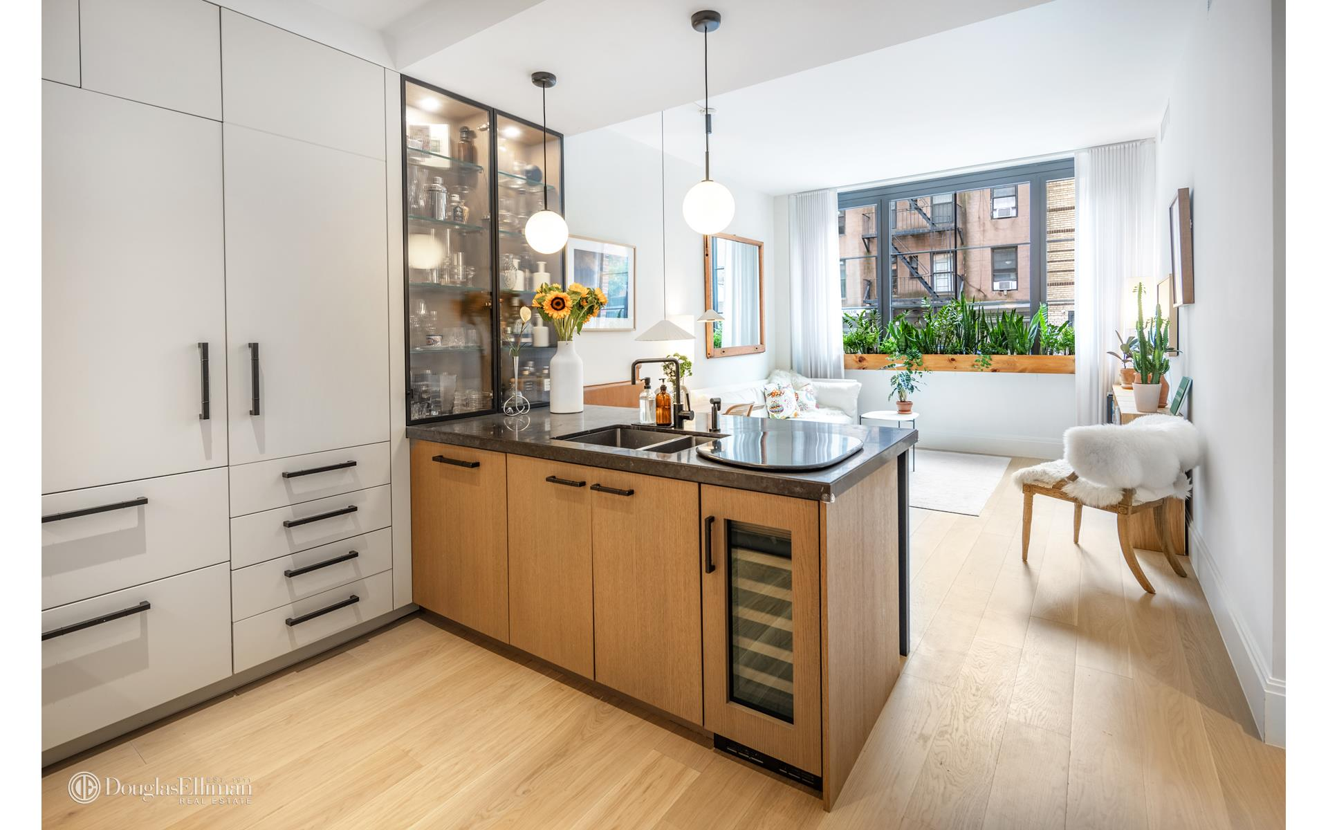 Welcome home to this luxurious residence with gorgeous southern light, high-ceilings, and stunning finishes throughout in the most sought after building in the East Village. This gorgeous apartment is designed with a beautiful south-facing primary bedroom   with a 2nd interior bedroom that is currently set up as child's room that can easily be used as a 2nd bedroom, guest room or home office.    A gracious foyer adorned with Menu lighting greets you into this 975 square foot residence designed by Paris Forino offering gorgeous, oversized casement windows framed in statuary bronze, soaring ceilings up to 10.5ft and a bright southern exposure. Exceptional   interior features include seven-inch-wide plank European white oak flooring, high interior doors with burnished brass hardware and custom architectural millwork throughout. Satin lacquer custom Italian cabinetry, limestone and Calacatta marble countertops,   Menu lighting and blackened metal hardware compose the expertly crafted kitchen equipped with appliances by Wolf, Bosch and Sub-Zero.    The master suite is a true sanctuary again with a light-filled southern exposure, generously sized to accommodate a king-sized bed, a walk-in closet with California closets and an en-suite master bath highlighted by luminous design details. The serene space   features Bianco Carrara honed mosaic floors and a Custom-cerused white oak vanity with a Bianco Dolomiti countertop.    The home office has been beautifully designed with custom glass door and wall that captures the essence of the casement windows allowing for privacy but still allowing light to come into the space. This room also includes a large closet outfitted with custom   California closets. A space that is perfect as an additional bedroom or office.     The dramatic powder room which is just off the living space offers watercolor glazed penny round mosaic walls, custom lighting, and a corner-wrapping vanity mirror. Chrome fittings by Waterworks are featured through